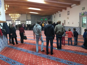 Visitors are watching Muslims praying at the Hurth Mosque near Cologne